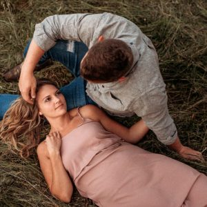 woman laying on mans lap in field