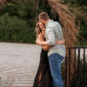 engaged couple under rustic arch