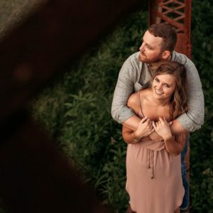 engaged couple hugging on rustic trestle