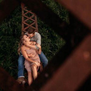 engaged couple cuddling on rustic trestle