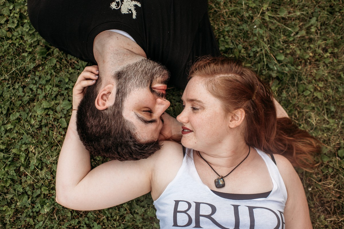 Engaged couple laying on ground snuggling